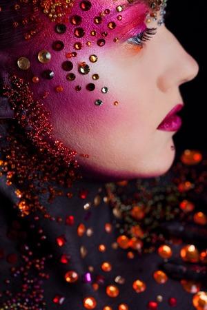 chica joven y atractiva en la luminosa arte del maquillaje, pintura de la carrocería. Perfil