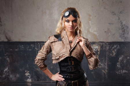 Portrait of a beautiful steampunk woman in Aviator glasses over grunge background.