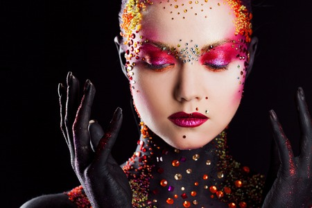 Young attractive girl in bright art-makeup, body painting. Profile