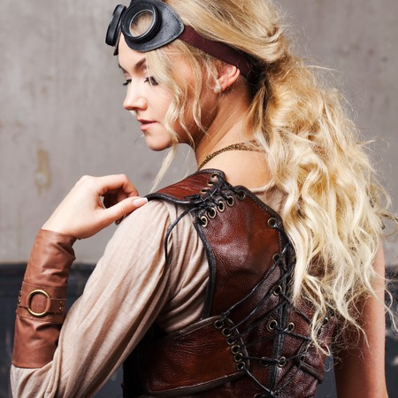 steampunk goggles: Portrait of a beautiful steampunk woman in Aviator glasses over grey background. Stock Photo
