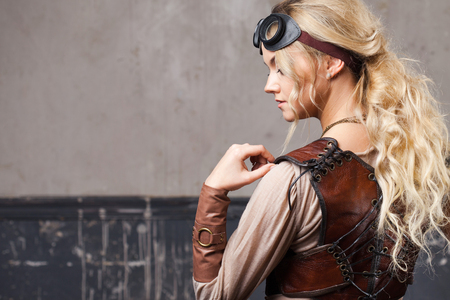 subculture: Portrait of a beautiful steampunk woman in Aviator glasses over grey background. Stock Photo