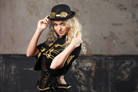 Portrait of a beautiful steampunk woman hat-bowler hat over grunge background.