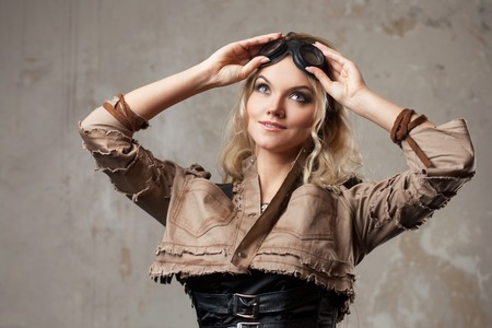 steampunk goggles: Portrait of a beautiful steampunk woman in Aviator glasses over grey background. Looking up
