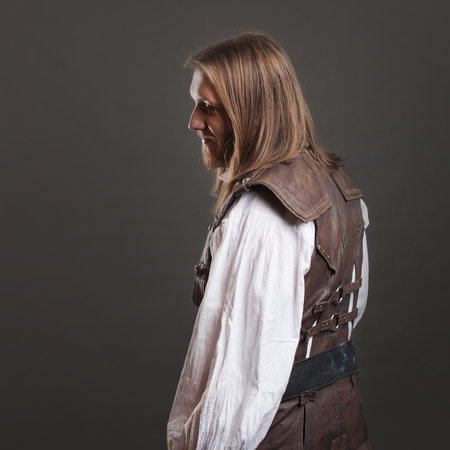 Handsome male Steam punk in a leather vest. Retro man portrait over gray background. Stock Photo
