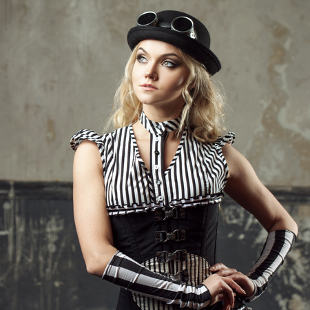 subculture: Portrait of a steampunk woman over grunge background. Beautiful lady in a Victorian style