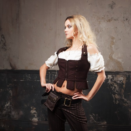 Portrait of a beautiful steampunk woman in a pant suit with vest, over grunge background. Stock Photo
