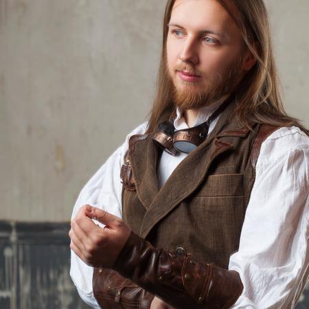 steampunk goggles: Handsome male Steam punk. Retro man portrait over grunge background.