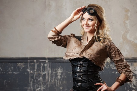 steampunk goggles: Portrait of a beautiful steampunk woman in Aviator glasses over grunge background.