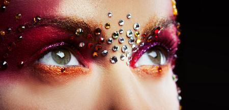 Ojos de una mujer joven y hermosa en un maquillaje de diseñador brillante con diamantes de imitación