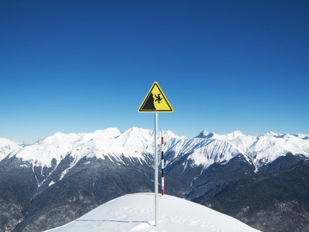 mortally: Yellow danger sign on ski slopes on the background of sky and winter mountains