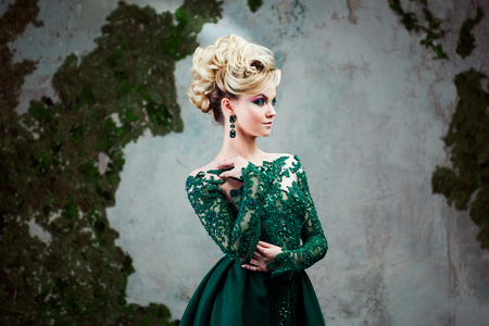 Portrait of young attractive blonde woman in a beautiful green dress. Textured background, interior. Luxury hairstyle