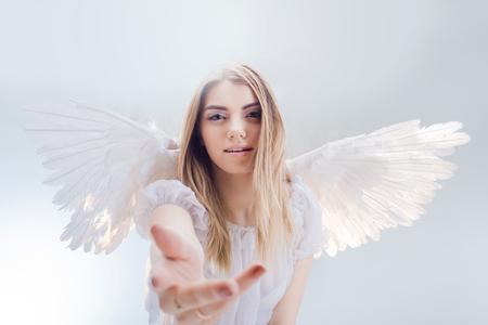 천사가 당신을 도와줍니다. 흰 날개를 가진 천사의 이미지에 영, 멋진 금발 소녀.
