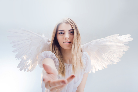 An angel from heaven gives you a hand. Young, wonderful blonde girl in the image of an angel with white wings. Stockfoto