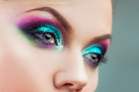 makeup eyes: Portrait of young attractive blonde woman. Makeup close-up, green and blue tone Stock Photo