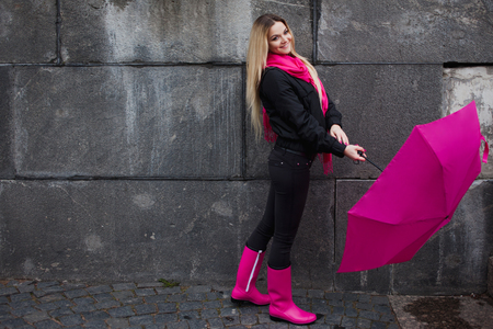 Mooie jonge en gelukkige blonde vrouw met kleurrijke paraplu op straat. Het concept van positiviteit en optimisme