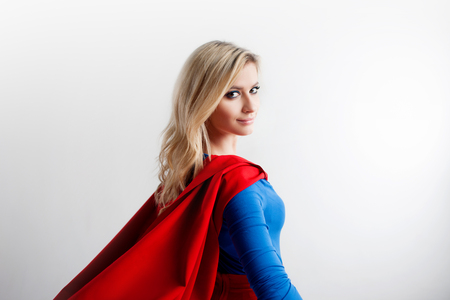 Superhero Woman looking off into the distance at right. Young and beautiful blonde in image of superheroine, back