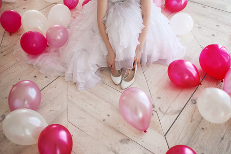 Young woman in wedding dress in luxury interior with a mass of pink and white balloons, sitting on the floor. Hold in hands her white shoes. Stock Photo