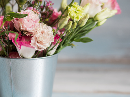 Spring flowers in small tin bucket. Bunch of different spring flowers in small tin bucket. Rustic wooden background