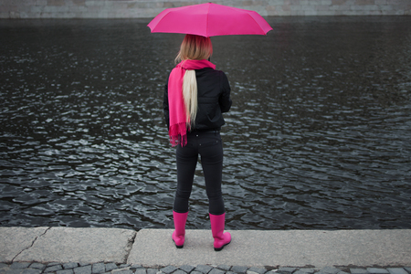 Girl in a bright pink scarf, rubber boots and umbrella standing on the banks of the river, back. Grey grim landscape.