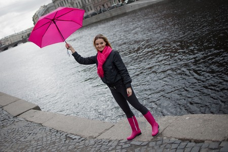 Beautiful young and happy blond woman in a bright pink scarf, rubber boots and umbrella walking in a rainy city. Stock Photo