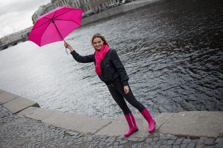 Mooie jonge en gelukkige blonde vrouw in een fel roze sjaal, rubberen laarzen en parasol lopen in een regenachtige stad. Stockfoto