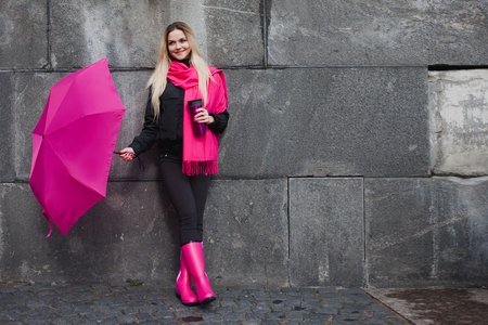 Beautiful young and happy blond woman with colorful umbrella on the street. The concept of positivity and optimism