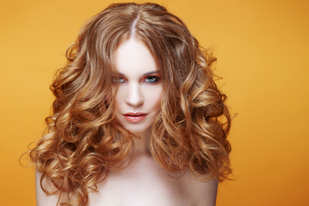 Beautiful redheaded girl with luxurious curly hair. Studio portrait on yellow background. Excellent hair Stock Photo