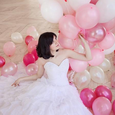 젊은 여자 핑크와 화이트 풍선의 질량과 럭셔리 인테리어에 웨딩 드레스에 바닥에 앉아. 세련 된 Quinceanera 드레스에서 짧은 머리와 매력적인 젊은 갈색 스톡 콘텐츠