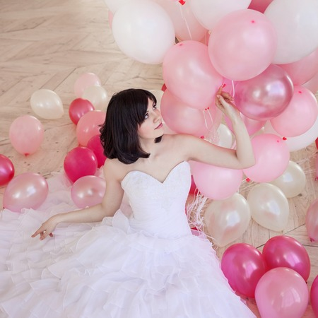 Young woman in wedding dress in luxury interior with a mass of pink and white balloons, sitting on the floor. Charming young bride brunette with short haircut in stylish Quinceanera dresses. Banque d'images