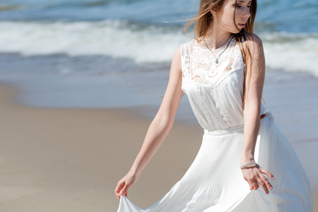 alongside: Young charming brunette woman on sea coast. Beautiful girl in a white summer dress. On the background of sea waves