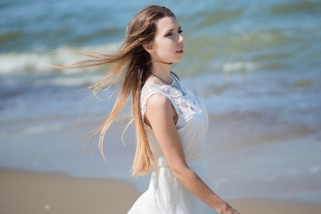 Young charming brunette woman on sea coast. Beautiful girl in a white summer dress. On the background of sea waves