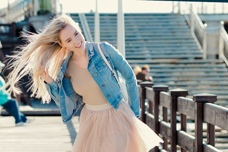 seaboard: Young cheerful girl on the seashore. Young blonde walk on the promenade.