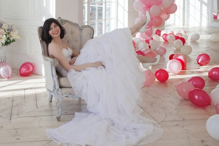 Young woman in wedding dress in luxury interior with a mass of pink and white balloons, sitting in the chair. Charming young bride brunette with short haircut in stylish Quinceanera dresses.