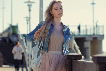 seaboard: Young cheerful girl on the seashore. Young blonde woman smiling. Trendy style
