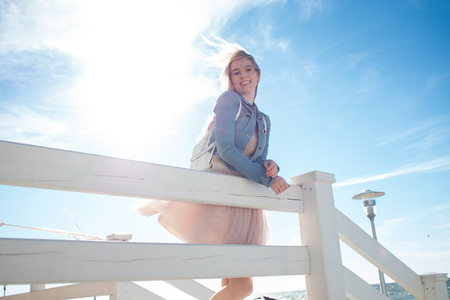 leaning over: Young cheerful girl on the seashore leaning over on the wooden white fence. Young blonde woman smiling. Trendy beige skirt
