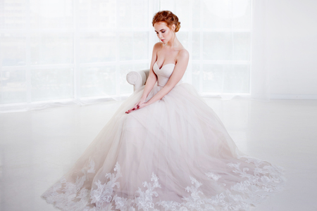 Portrait of a beautiful girl in a wedding dress. Bride in luxurious dress sitting on a chair