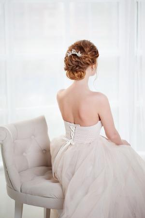 De mooie roodharige bruid zit als voorzitter, modieus kapsel, achtermening. Jonge vrouw in luxueuze huwelijkskleding Stockfoto