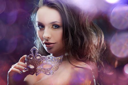 顔に紫色のマスクと美しい若いブルネット。カーニバル、お祝い。輝くブルーと紫のまぶしさの抽象的な背景は。