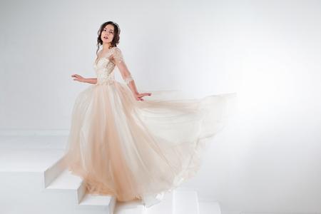 웨딩 드레스의 아름 다운 여자의 초상화. 계단에 서있는 고급스러운 드레스의 신부가 등반한다.