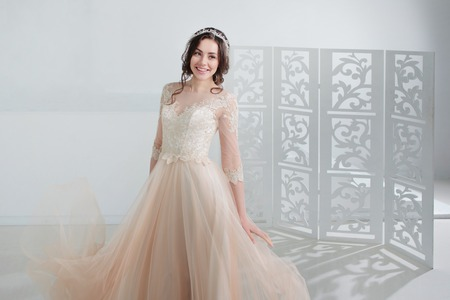 Portrait of a beautiful girl in a wedding dress. Bride in a luxurious dress, in a beautiful white interior