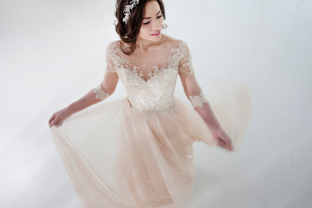 아름 다운 소녀는 웨딩 드레스에서 춤. 흰색 배경에 고급스러운 드레스의 신부