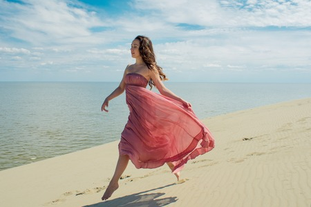 Woman in red waving dress with flying fabric runs on background of dunes. Skyline and the sea Stock Photo