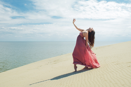 Woman in red waving dress with flying fabric runs on background of dunes. Gymnast on the back of the dune Stock Photo