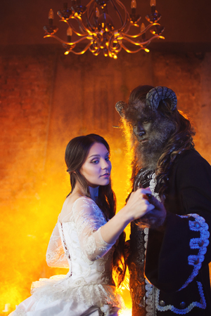 Fine art photo of beauty and beast. Beautiful girl and a monster, dance