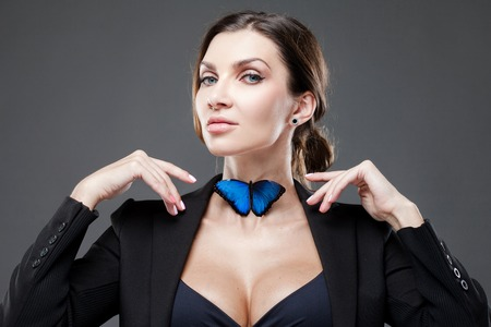 Bow tie concept. Beautiful lady adjusts her blue butterfly on the neck