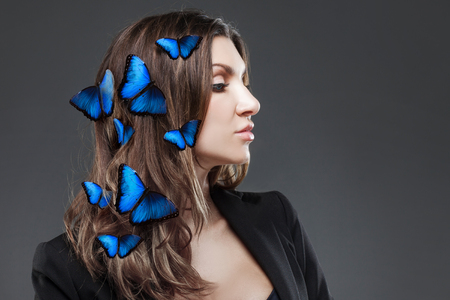 flit: Beauty Fashion Model Girl with a large number of butterflies in hair. Grey background