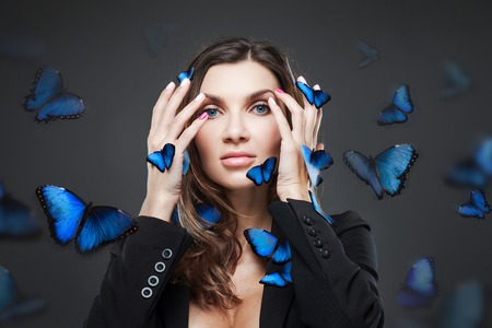 flit: Beauty Fashion Model Girl surrounded by swarms of butterflies. Grey background Stock Photo