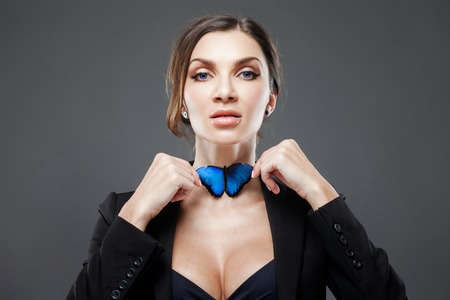 Bow tie concept. Beautiful lady adjusts her blue butterfly on the neck Zdjęcie Seryjne - 82314675