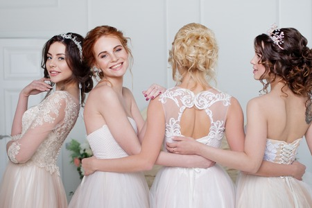 Bride in wedding salon. Four beautiful girl are in each others arms. Back, close-up lace skirts