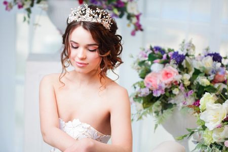 hair stylist: Portrait, wedding hair style, brunette with curly hair. Beautiful girl in a wedding dress. Close-up